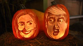 Styrofoam carvings on display while this year carving of 2016  Democratic nominee Hillary Clinton and Republican presidential nominee Donald Trump in pumpkin form  are being worked on by Pumpkin carver Hugh McMahon as he visits Chelsea Market in New York to complete his annual carving of a giant pumpkin,October 28, 2016. / AFP / TIMOTHY A. CLARY        (Photo credit should read TIMOTHY A. CLARY/AFP/Getty Images)