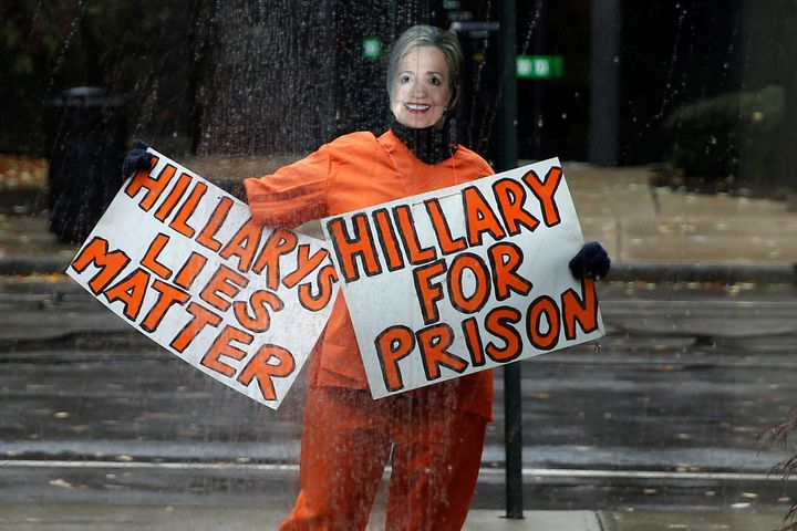 A person wearing an orange jumpsuit and dressed as Hillary Clinton stands outside Donald Trump's campaign event in Manchester