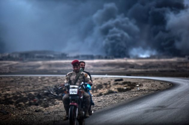 An Iraqi soldier and a civilian ride a motorbike as smoke rises behind them, on the road between Qayyarah...