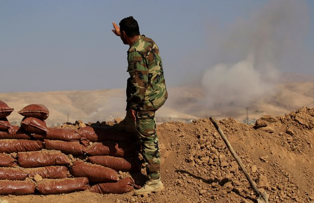 A Kurdish Peshmerga soldier who is stationed between two front lines gestures as a smoke rises near Bashiqa,...