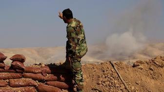 A Kurdish Peshmerga soldier who is stationed between two front lines gestures as a smoke rises near Bashiqa, east of Mosul, Iraq October 29, 2016. REUTERS/Zohra Bensemra