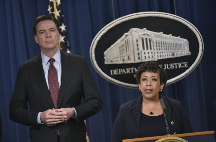 FBI Director James Comey, left, stands alongside Attorney General Loretta Lynch during a press conference at the Departm