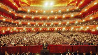 General view of the audience and the Metropolitan Opera Orchestra, with American artistic director and conductor James Levine, on the opening night of the 1997-1998 season at Lincoln Center's Metropolitan Opera House, New York, New York, September 22, 1997. (Photo by Jack Vartoogian/Getty Images)