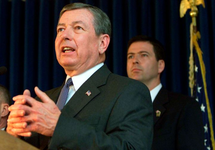James Comey, then U.S. Attorney for the Southern District of New York, stands behindAttorney General John Ashcroft as h