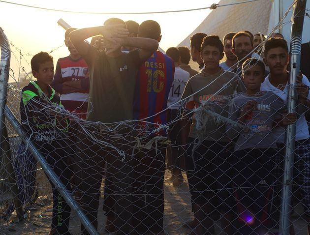 Iraqi men and boys stand inside of a fenced-in area next to a screening center at Debaga camp. Some...