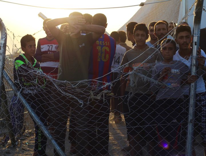 Iraqi men and boys stand inside of a fenced-in area next to a screening center at Debaga camp. Some are detained there f