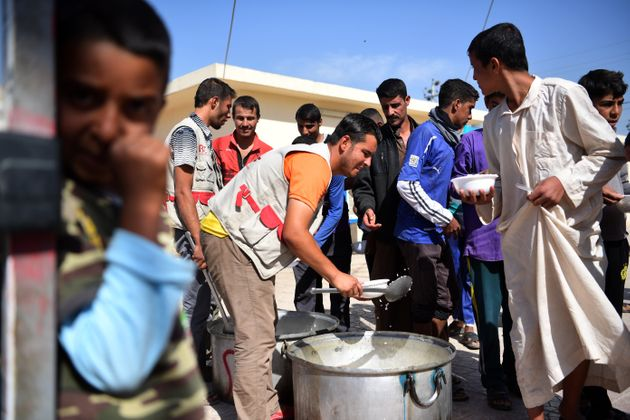 Displaced Iraqi men wait for food at Debaga camp on Oct. 21. Newly arrived men, women and children...