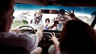 Mature Couple being attacked in their car by a hoard of zombies.