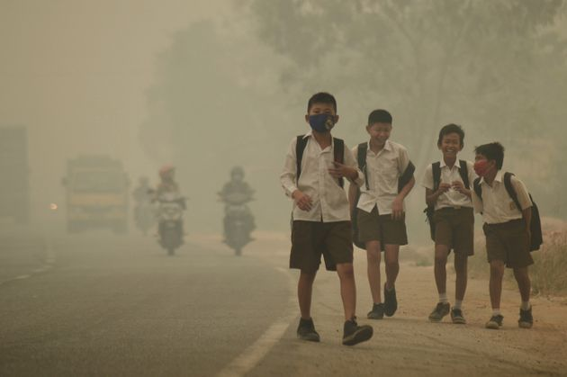 Students walk along a street as they are released from school to return home earlier due to the haze...