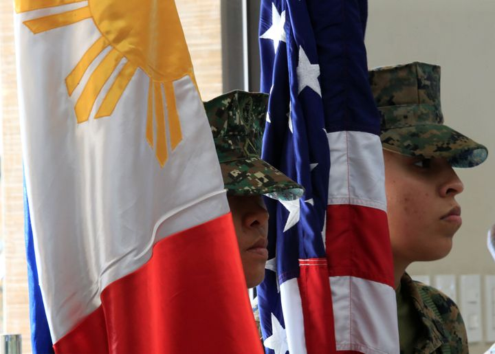 Philippine-U.S. marine corps stand at attention with the Philippine and American flags.