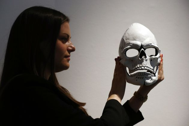 A woman poses with the mask from James Bond's Day of the Dead costume, worn by Daniel Craig in
