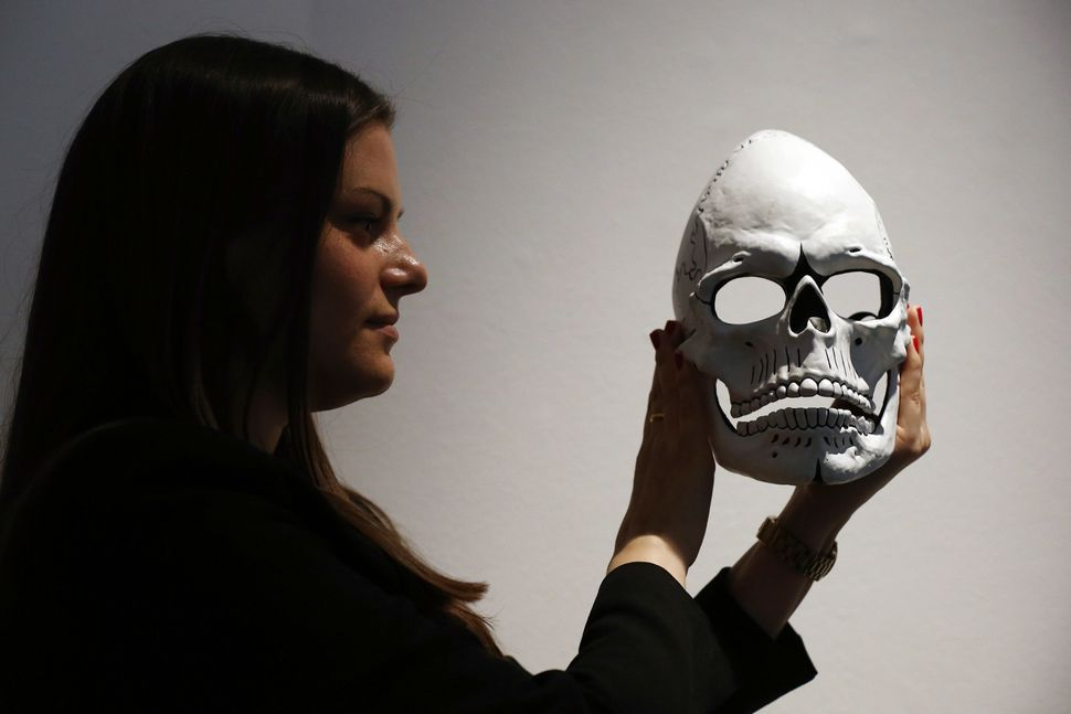 "A woman poses with the mask from James Bond's Day of the Dead costume, worn by Daniel Craig in ""Spectre,"" during a photocall"