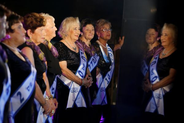 Some contestants are reflected in a marble column (R) during the annual Holocaust survivors' beauty pageant in the Israeli ci