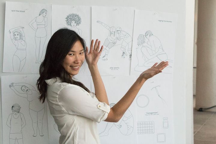 The creator of the Period Coloring Book, Andrea Yip, with her illustrations.