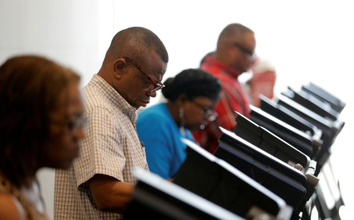 A voter casts his ballot during early voting at the Beatties Ford Library in Charlotte, North Carolina, on Oct. 20, 2016.