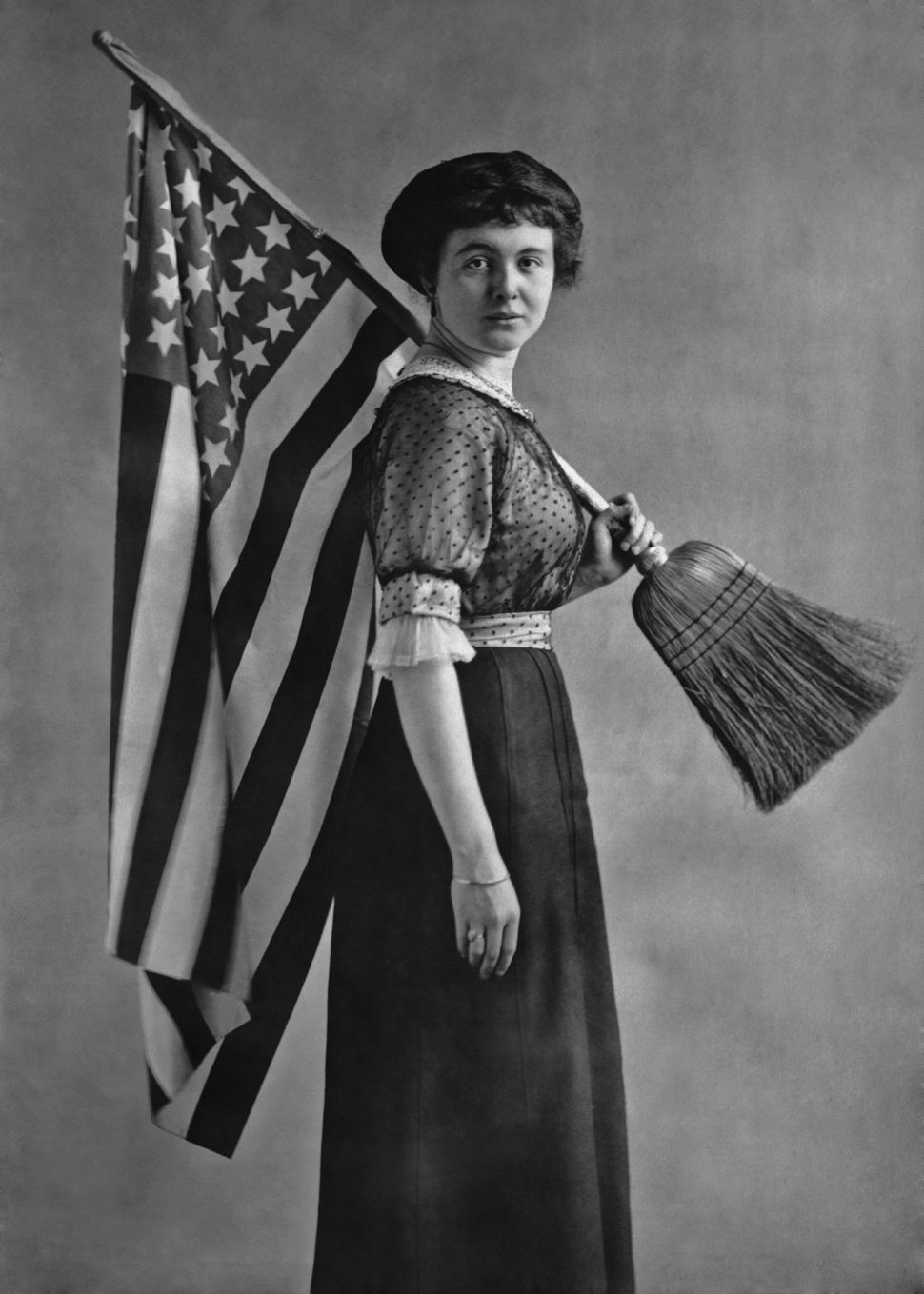An American suffragette carries a U.S. flag attached to a broom handle.