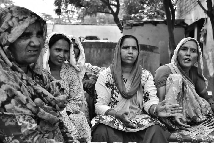 Mewat Radio supervisor and senior reporter Sunita Mishra, center, sits with Hoora Begum, second from left, and other women to