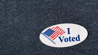Closeup of an American 'I voted' sticker placed on a navy shirt.