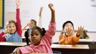 School children raising their hands in class