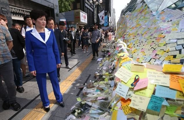 South Korean Gender Minister Kang Eun-hee looks at Post-it messages on the wall of a subway exit in Gangnam,...