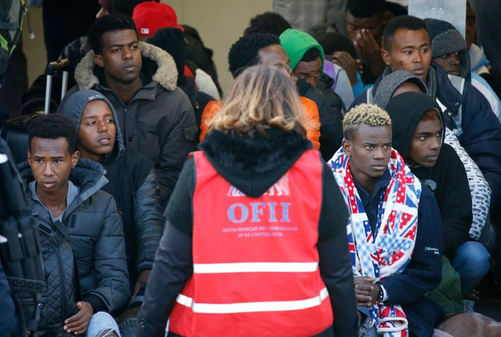 Migrant minors queue to take a bus before their transfer by French authorities to reception centres across the country at the