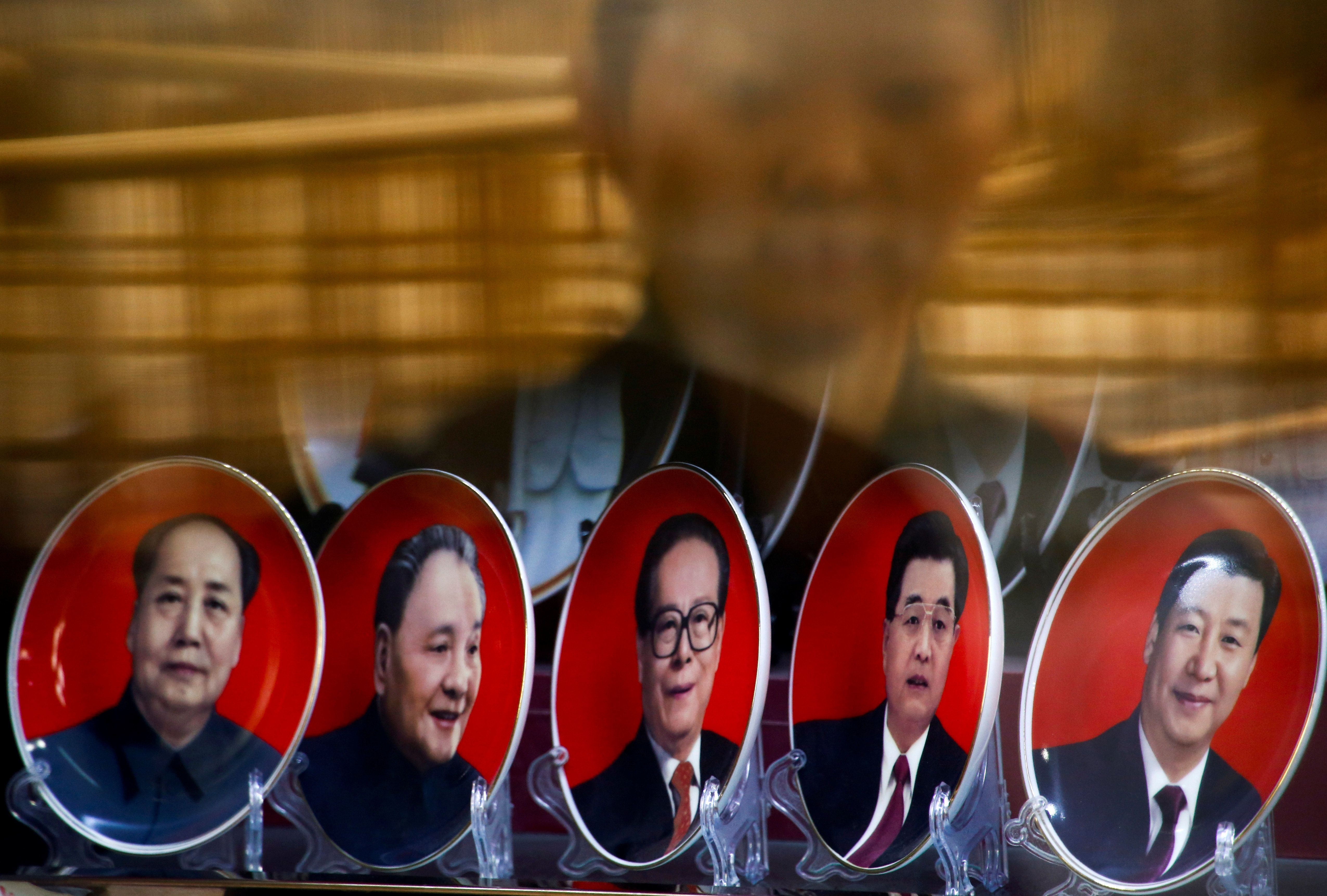 A woman is reflected in a shop window as she looks at souvenir plates with portraits of former Chinese leaders Mao Zedong, Deng Xiaoping, Jiang Zemin, Hu Jintao and current President Xi Jinping (L-R) on the second day of plenary sessions of the 18th Central Committee of the Communist Party of China (CPC) in Beijing, China, October 25, 2016.  REUTERS/Thomas Peter