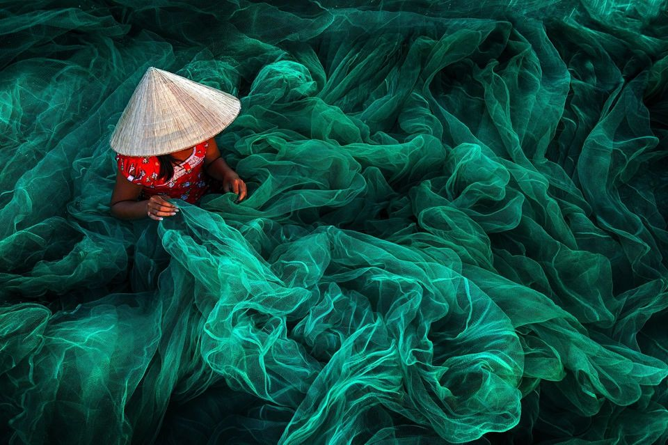 A woman creates a fishing net in a small village near Phan Rang.