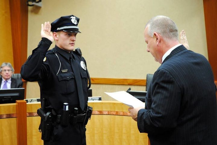 Urbandale Police Officer Justin Martin, one of the two officers killed in Wednesday's attacks in Iowa, raises his hand
