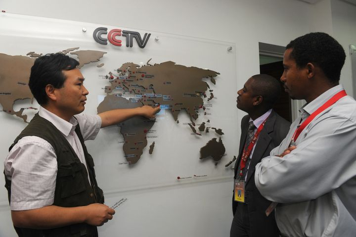 Aneditor of CCTV Africa in Nairobi talks to a local journalist as he shows how the organization has expanded in differe