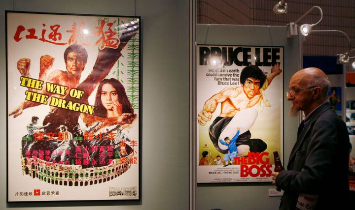 A visitor looks at movie posters during the opening of a Bruce Lee exhibition as part of the Hong Kong International Film Fes