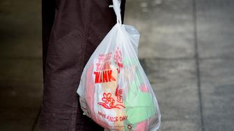 A pedestrian carries a single-use plastic bag while shopping in the Chinatown section of Los Angeles, California, U.S., on Tuesday, June 24, 2014. California grocers, who could realize $1 billion in new revenue from selling paper bags for a dime each, are teaming up with environmentalists on a new push to make California the first state to ban plastic shopping bags. The retail and environmental lobbies, which backed many of 13 failed California bills since 2007 to curb or ban single-use plastic shopping bags, are facing off against manufacturers of both plastic and paper bags who oppose restrictions on the sacks. Photographer: Kevork Djansezian/Bloomberg via Getty Images