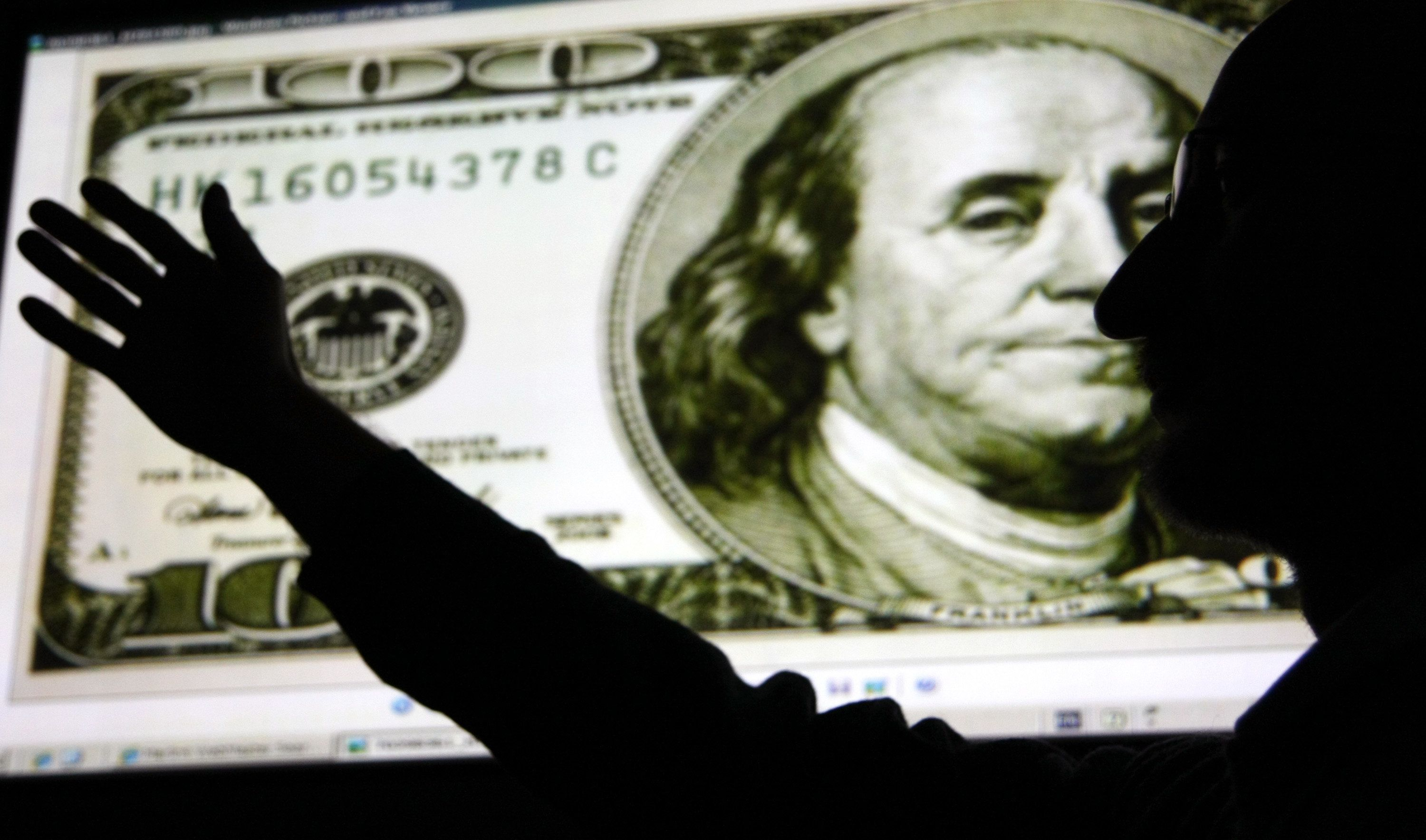 A man, silhouetted in front of an image of a 100 U.S. dollar note displayed on a monitor, poses for a photograph in Tokyo, Japan, on Wednesday, Dec. 29, 2010. The dollar traded near a six-week low against the yen as U.S. data signaled an uneven recovery in the world's largest economy. Photographer: Tomohiro Ohsumi/Bloomberg via Getty Images