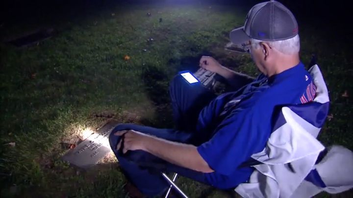 Wayne Williams listens to the World Series at his father's grave in Indiana.