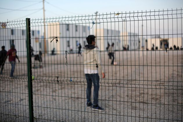 Young migrants play football near the Calais
