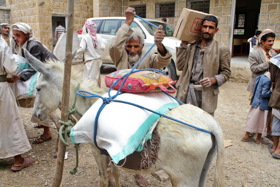 A father carries home his monthly ration of food items provided by Mercy Corps through its voucher system that works with loc