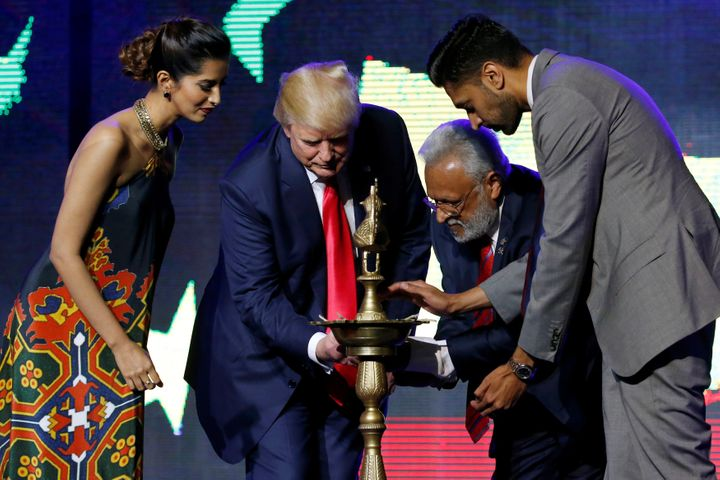 Republican Hindu Coalition Chairman Shalli Kumar (2nd R) helps Republican presidential nominee Donald Trump (2nd L) light a c