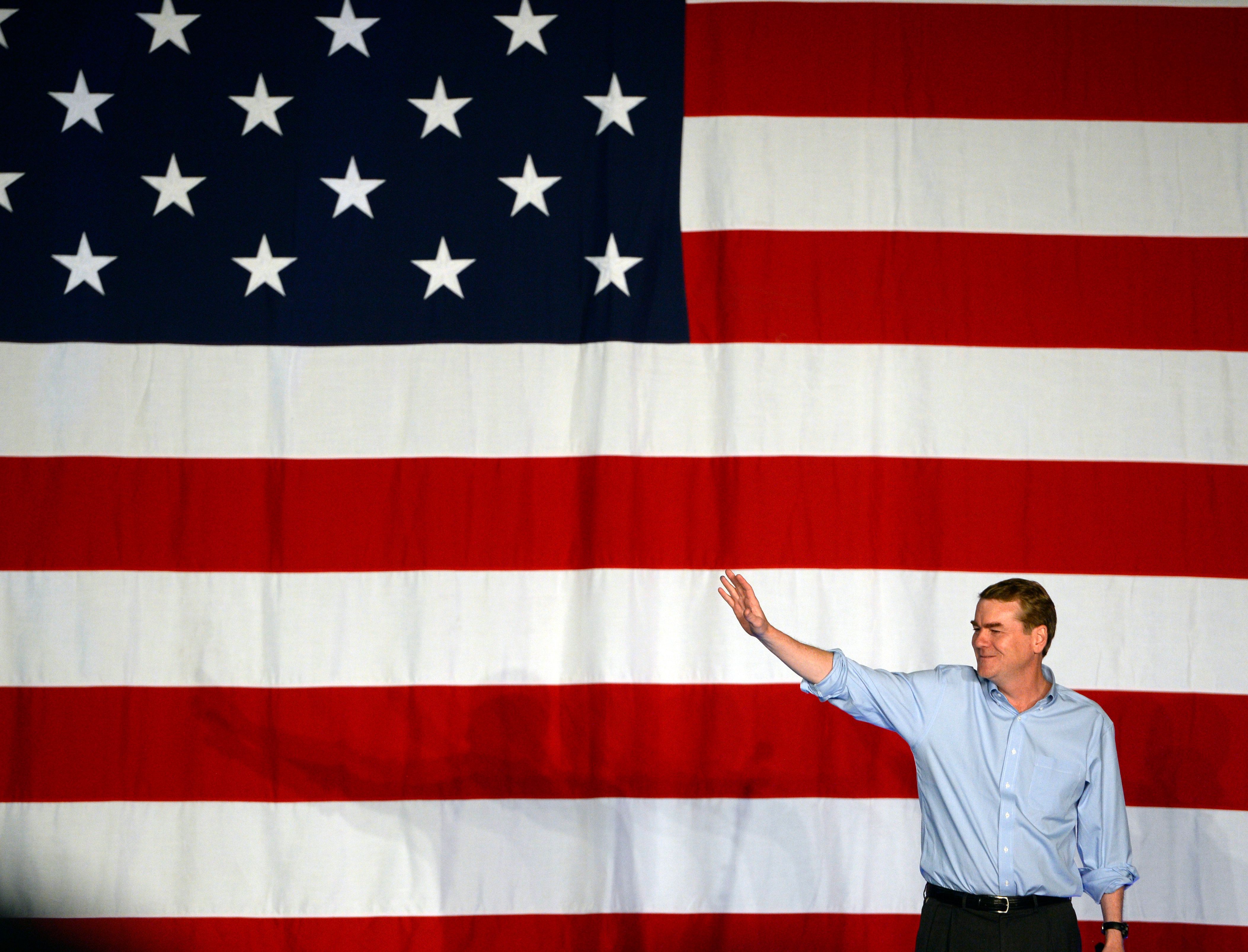 Sen. Michael Bennet waves to the crowd at a rally at Denver's National Western Complex on Oct. 10. Colora