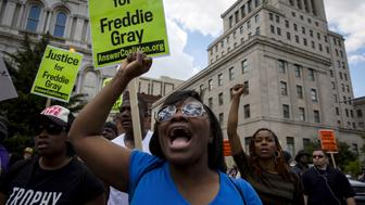 People gather at city hall in Baltimore, Maryland May 2, 2015. A jubilant Baltimore headed into a weekend of rallies after six police officers were criminally charged over the arrest of 25-year-old black man Freddie Gray whose death led to rioting earlier in the week. REUTERS/Eric Thayer