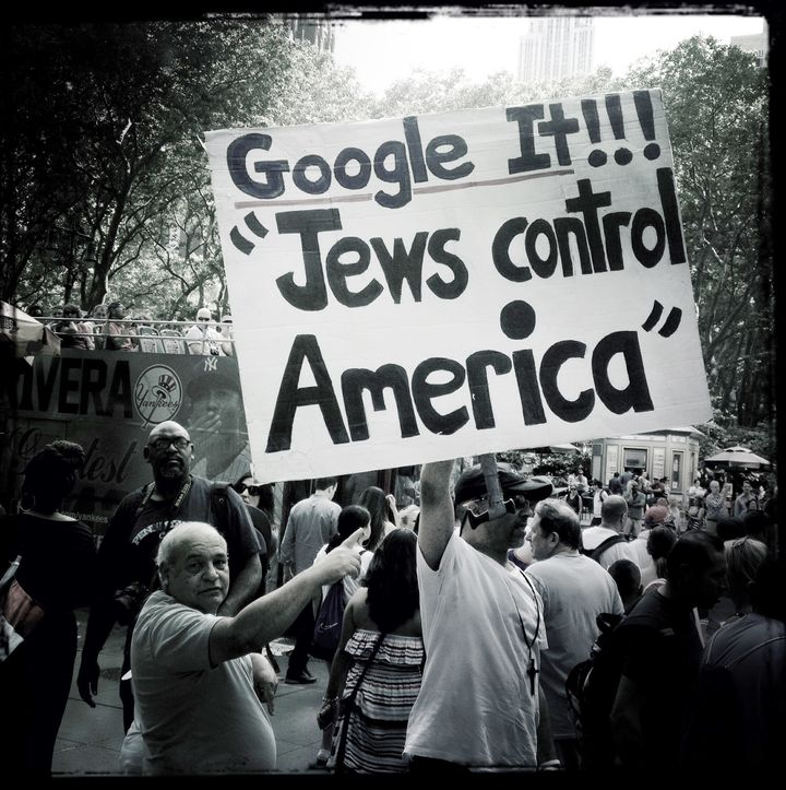 A man holds up an anti-Semitic sign on a crowded Manhattan street.