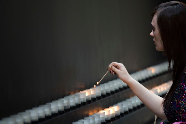 A visitor lights a memorial candle at the United States Holocaust Memorial Museum, May 2, 2016.