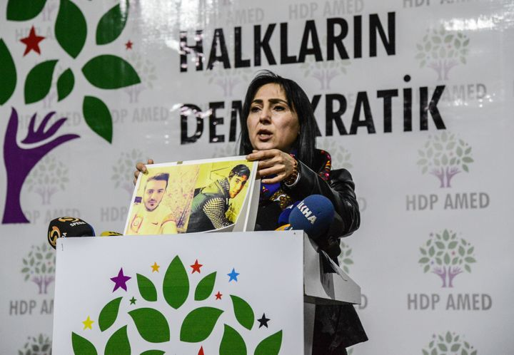 Figen Yuksekdag, co-leader of the pro-Kurdish Peoples' Democratic Party holds pictures of killed demonstrators at a funeral c