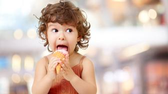 Kid eating ice cream in cafe.