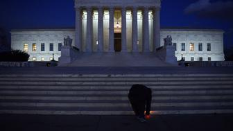 WASHINGTON, DC - FEBRUARY 13: A young man places a candle light  in front of the U.S. Supreme Court in Washington, D.C., February 13, 2016, after the death of Supreme Court Justice Antonin Scalia. Scalia died today on a ranch near San Antonio, TX. He was 79. (Photo by Astrid Riecken For The Washington Post via Getty Images)
