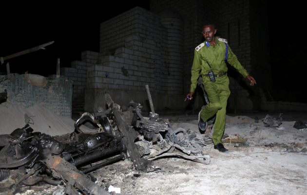 A Somali policeman inspects the scene of a suicide car explosion near the parliament in the capital Mogadishu,...