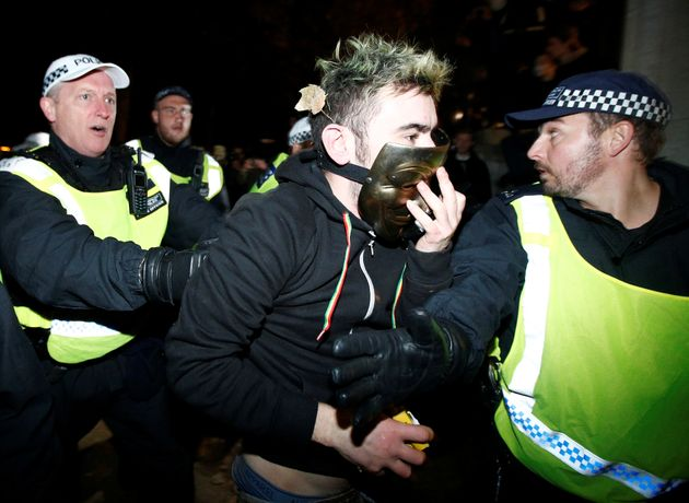 Police detain a protester during the Million Mask March in