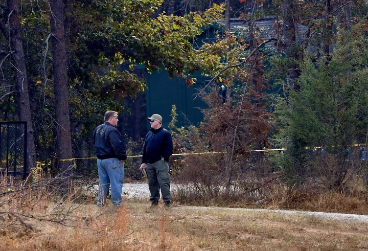 Authorities are seen standing near the suspect's property in Woodruff, where they say a woman was found chained inside of a s