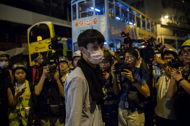 Newly elected lawmaker Baggio Leung (C) of Youngspiration stands in front of the press in Hong Kong early...