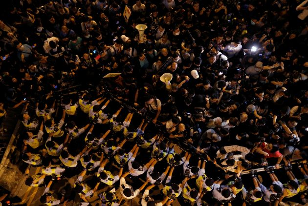 Police stop demonstrators as they protest against what they call Beijing's interference over local politics...
