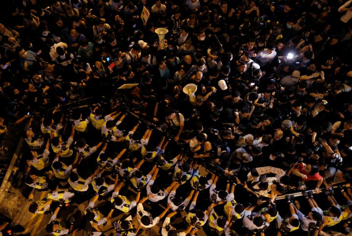 Police stop demonstrators as they protest against what they call Beijing's interference over local politics and the rule of l