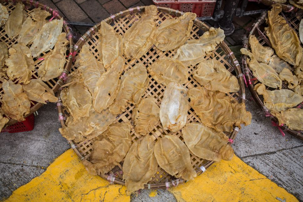 This March 2016 photo shows fish maws placed in a basket to dry outside a dried goods shop in Hong Kong. The maws of totoaba,